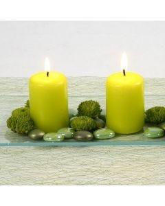 Bloklys i limegrøn arrangeret med dekorationssten på glasfad