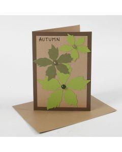Brunt kort dekoreret med udstansede blade af karton