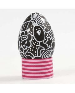 Sort påskeæg med hvide doodle tegninger i æggebæger af karton