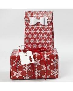 Julegaveindpakning med snefnug motiver pyntet med sløjfe og manillamærke