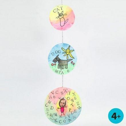 Mobile af runde kartonskiver med vandfarve, aftryk og tegninger