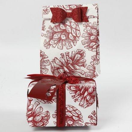 Julegaveindpakning med grankogle motiver pyntet med sløjfe og bånd