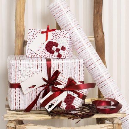 Julegaveindpakning i rød og hvid pyntet med julehjerte, snefnug og julesok lavet af rørperler