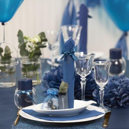 Borddækning og bordpynt i mørk blå med papirblomster, balloner, serviet foldet som tårn og bordkort