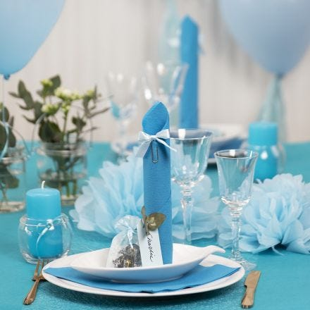Borddækning og bordpynt i lyseblå med papirblomster, balloner, serviet foldet som tårn og bordkort