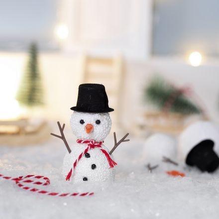 Nissen bygger en snemand foran sin nissedør
