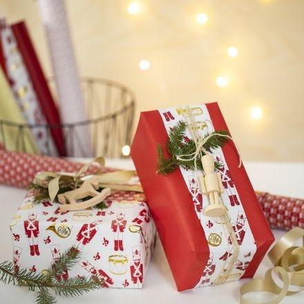 Kreativ julegaveindpakning med to slags gavepapir og en træfigur