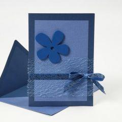 Kort i blåt pyntet med blomst, bånd og net fra bordløber