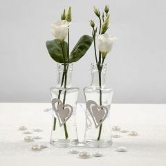 Vase dekoreret med hvidt satinbånd og hjerte