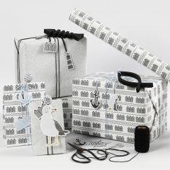 Gaveindpakning i sort, hvid og sølvglitter med karton mærkater, fisk af træ og shaker clips