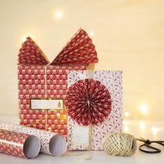 Julegaveindpakning med papirvifte og -rosette