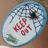 Dørskilt af træ dekoreret med maling samt edderkopper og kryb af plast