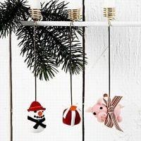 Lyseholder pyntet forskelligt med hhv. snemand, julegave og julegris af cernit