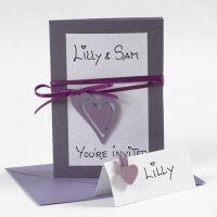 Indbydelse og kuvert i hvid og lilla med hjerter i træ og satinbånd