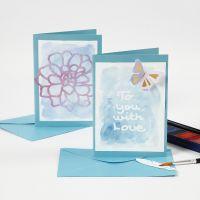 Kort og bordkort med tekst af tegnegummi malet over med akvarelfarve