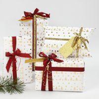 Julegaveindpakning i hvid og guld pyntet med bånd og figurer i bonzaitråd