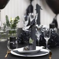 Borddækning og bordpynt i sort med papirblomster, balloner, serviet foldet som tårn og bordkort