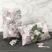 Gaveæske pyntet med lyserødt bånd, metalring og blomster mærkater